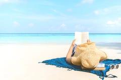 Donna di festa della spiaggia di estate che legge un libro sulla spiaggia a tempo il tempo libero immagini stock