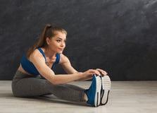 Donna di forma fisica ad allungare addestramento alla palestra Fotografia Stock