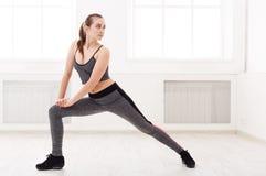 Donna di forma fisica ad allungare formazione all'interno Immagini Stock Libere da Diritti