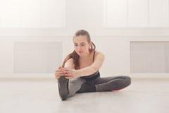 Donna di forma fisica ad allungare formazione all'interno Fotografie Stock