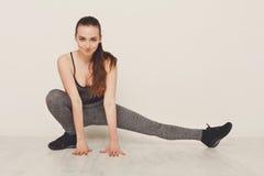 Donna di forma fisica ad allungare formazione all'interno Immagini Stock