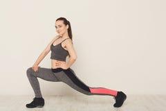 Donna di forma fisica ad allungare formazione all'interno Fotografia Stock