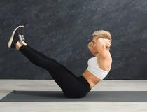 Donna di forma fisica che allunga al fondo grigio all'interno Fotografia Stock