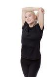 Donna di forma fisica che allunga armi Fotografia Stock