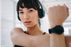 Donna di forma fisica che allunga armi al club di salute Fotografia Stock Libera da Diritti