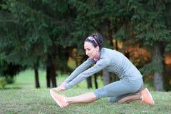Donna di forma fisica che allunga la sua gamba per scaldarsi all'aperto Immagine Stock Libera da Diritti
