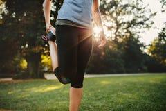 Donna di forma fisica che allunga le gambe in parco Fotografia Stock Libera da Diritti