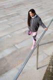 Donna di forma fisica che allunga le gambe prima dell'allenamento urbano Fotografia Stock