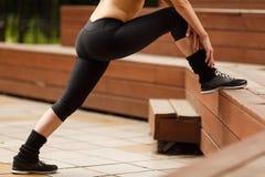 Donna di forma fisica che allunga le gambe prima della formazione all'aperto Immagine Stock