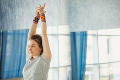 Donna di forma fisica che allunga le sue mani che esercitano yoga in corridoio Immagine Stock