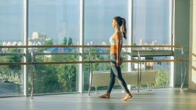 Donna di forma fisica che allunga nella palestra sbarra Fotografie Stock