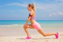 Donna di forma fisica che allunga prima dell'allenamento sulla spiaggia Fotografia Stock Libera da Diritti
