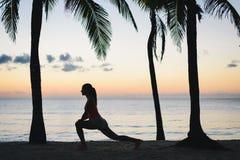 Donna di forma fisica che allunga sulla spiaggia di mattina Fotografia Stock