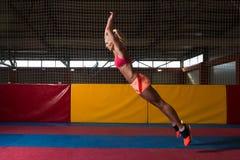 Donna di forma fisica che esegue un salto in lungo nella palestra Immagine Stock