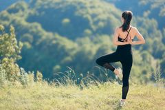 Donna di forma fisica che esercita flessibilità ed equilibrio in bella natura Immagini Stock