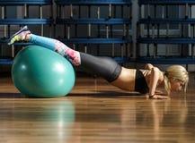 Donna di forma fisica che fa allenamento dell'ABS con una palla Fotografia Stock
