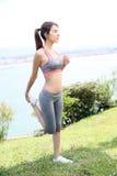 Donna di forma fisica che fa allungamento dalla spiaggia Fotografia Stock