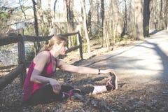 Donna di forma fisica che fa allungamento durante l'allenamento all'aperto di addestramento Fotografia Stock Libera da Diritti