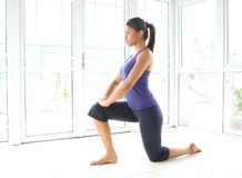Donna di forma fisica che fa allungamento per il tendine del ginocchio Fotografie Stock Libere da Diritti