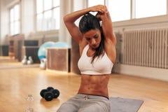 Donna di forma fisica che fa allungando esercizio alla palestra Fotografie Stock