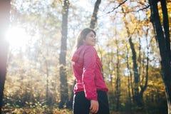 Donna di forma fisica che fa durante l'allenamento nella foresta di autunno Fotografia Stock Libera da Diritti