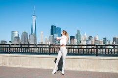 Donna di forma fisica che fa esercizio di allungamento che allunga le sue armi prima della formazione Fotografia Stock