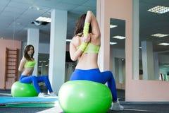 Donna di forma fisica che fa esercizio e che allunga su una palla di forma fisica Immagini Stock Libere da Diritti