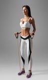 Donna di forma fisica che fa gli esercizi di allenamento per le mani e la parte posteriore con l'estensore Fotografie Stock Libere da Diritti
