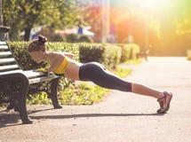 Donna di forma fisica che fa gli esercizi durante l'allenamento all'aperto di addestramento trasversale Fotografie Stock Libere da Diritti