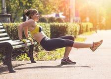 Donna di forma fisica che fa gli esercizi durante l'allenamento all'aperto di addestramento trasversale Immagine Stock