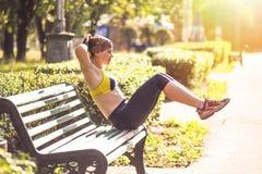 Donna di forma fisica che fa gli esercizi durante l'allenamento all'aperto di addestramento trasversale Fotografia Stock