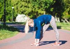 Donna di forma fisica che fa gli esercizi durante l'allenamento all'aperto di addestramento trasversale nella mattina soleggiata Immagini Stock