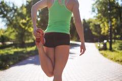 Donna di forma fisica che fa gli esercizi durante l'allenamento all'aperto di addestramento trasversale nella mattina soleggiata Fotografia Stock Libera da Diritti