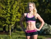 Donna di forma fisica che fa gli esercizi durante l'allenamento all'aperto di addestramento trasversale nella mattina soleggiata Immagini Stock Libere da Diritti