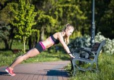 Donna di forma fisica che fa gli esercizi durante l'allenamento all'aperto di addestramento trasversale nella mattina soleggiata Immagine Stock