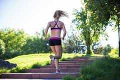 Donna di forma fisica che fa gli esercizi durante l'allenamento all'aperto di addestramento trasversale nella mattina soleggiata Fotografia Stock
