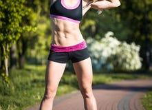 Donna di forma fisica che fa gli esercizi durante l'allenamento all'aperto di addestramento trasversale nella mattina soleggiata Fotografie Stock