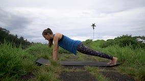 Donna di forma fisica che fa gli esercizi di yoga Posa femminile della plancia di addestramento archivi video