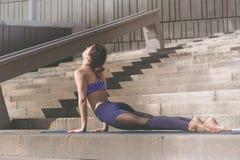 Donna di forma fisica che fa pratica urbana di yoga all'aperto Yoga di pratica della ragazza in buona salute sulla passeggiata de Immagini Stock
