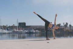 Donna di forma fisica che fa pratica urbana di yoga all'aperto Yoga di pratica della ragazza in buona salute sulla passeggiata de Fotografie Stock