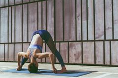Donna di forma fisica che fa pratica urbana di yoga all'aperto Yoga di pratica della ragazza in buona salute sulla passeggiata de Fotografie Stock Libere da Diritti