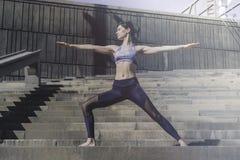 Donna di forma fisica che fa pratica urbana di yoga all'aperto Yoga di pratica della ragazza in buona salute sulla passeggiata de Immagine Stock Libera da Diritti