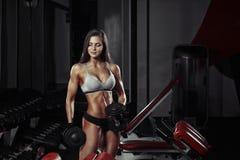 Donna di forma fisica che fa un allenamento di forma fisica con le teste di legno nella palestra Fotografia Stock
