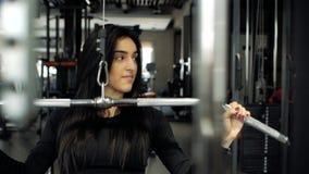 Donna di forma fisica che fa un'ampia presa mentre sedendosi sul simulatore Ragazza castana che fa gli esercizi nella palestra su video d archivio