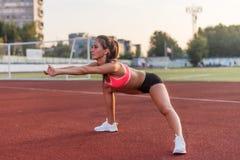 Donna di forma fisica che fa un riscaldamento prima del suo cardio allenamento di addestramento Immagini Stock