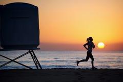 Donna di forma fisica che funziona sulla spiaggia Immagini Stock