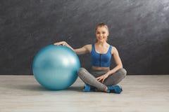 Donna di forma fisica che ha resto vicino alla palla di forma fisica Fotografie Stock Libere da Diritti