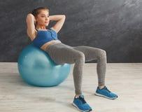 Donna di forma fisica che lavora all'ABS con la palla di forma fisica Fotografie Stock Libere da Diritti