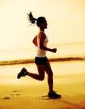 donna di forma fisica che pareggia alla spiaggia tramonto/di alba Immagine Stock