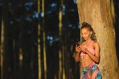 Donna di forma fisica che prende un resto per mandare un sms sullo smartphone Immagini Stock Libere da Diritti